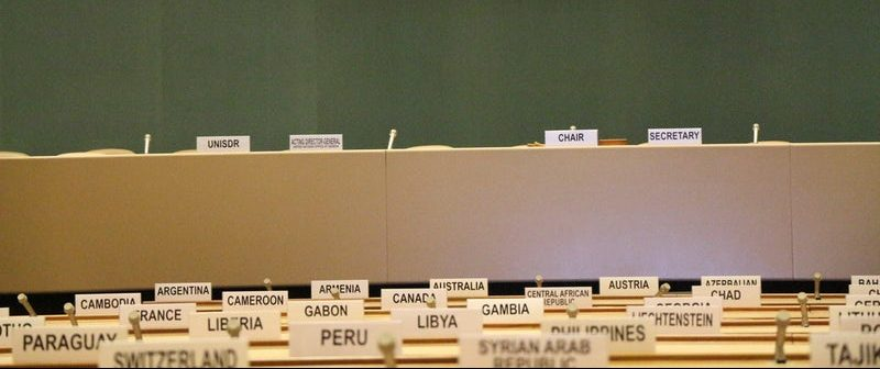 A picture of country placards on tables in a United Nations meeting room representing the need for multilingual accessibility.