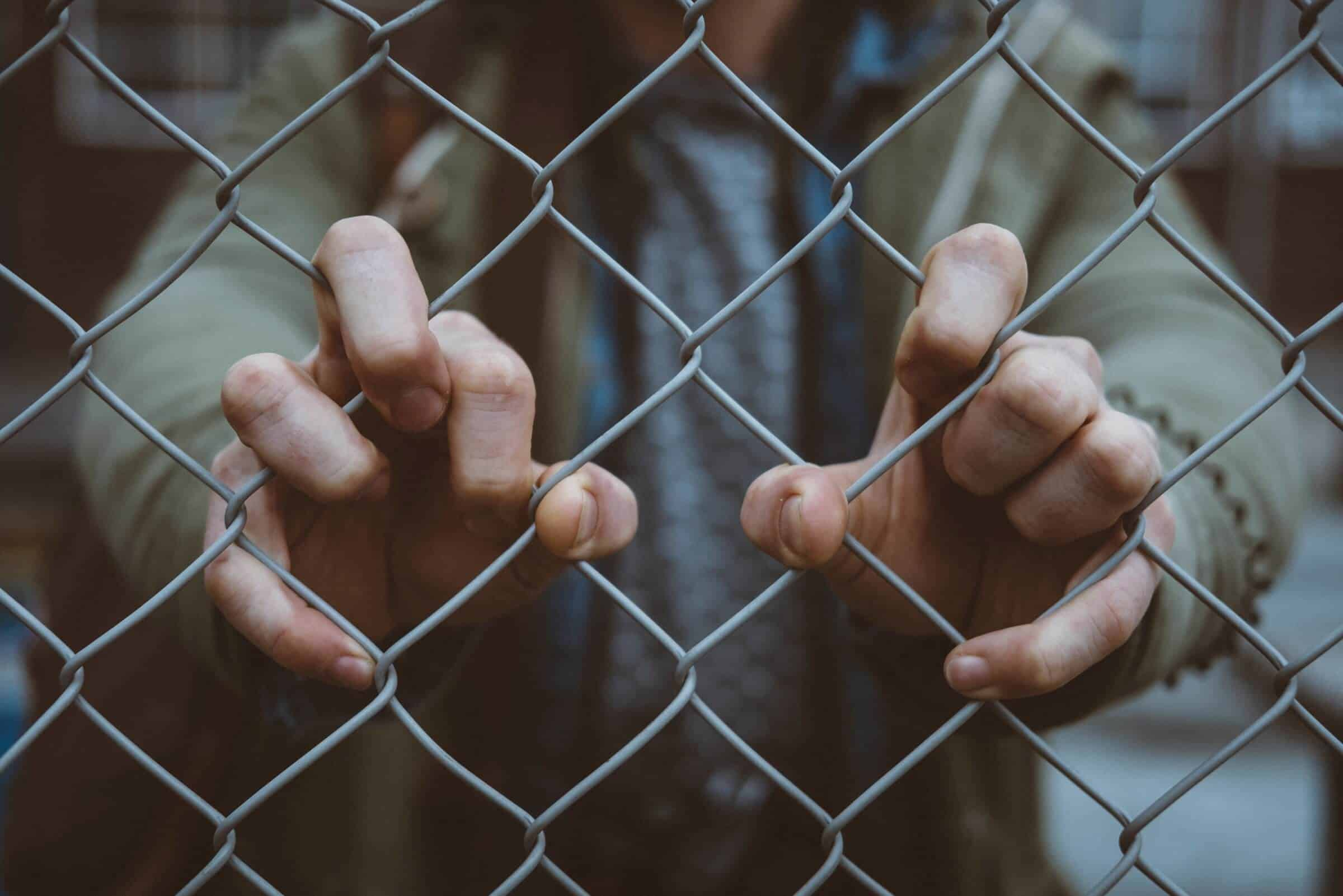 Image of man holding on to chain link fence as though he is barred from entry