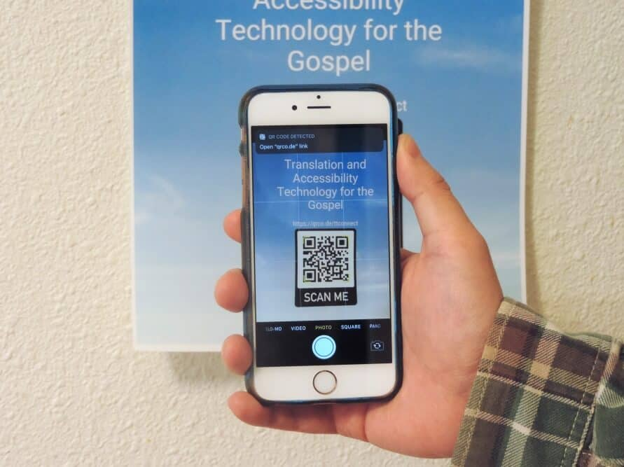 Hand holding smartphone to scan QR code