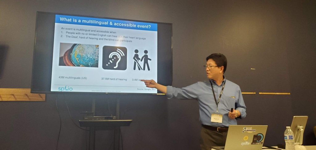 A picture of a man giving a presentation and pointing to a TV